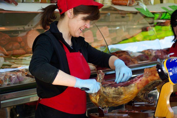 Bouchère coupant la viande dans une boucherie