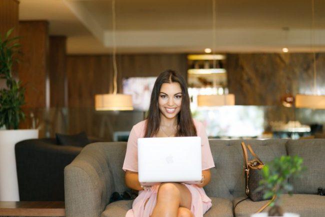 fille souriante assis sur un canapé avec son ordinateur